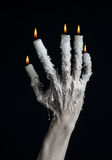 Halloween theme: on the hand wearing a candle and dripping melted wax on black isolated background Royalty Free Stock Image