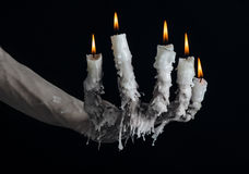 Halloween theme: on the hand wearing a candle and dripping melted wax on black isolated background Stock Photos