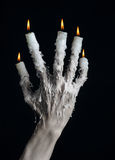 Halloween theme: on the hand wearing a candle and dripping melted wax on black isolated background Royalty Free Stock Photography