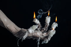 Halloween theme: on the hand wearing a candle and dripping melted wax on black isolated background Stock Photography
