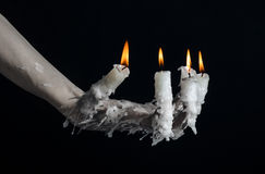 Halloween theme: on the hand wearing a candle and dripping melted wax on black isolated background Stock Images