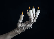 Halloween theme: on the hand wearing a candle and dripping melted wax on black isolated background Royalty Free Stock Photo