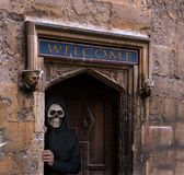 Halloween theme of man with skull mask welcoming to haunted house Stock Photos
