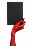 Halloween theme: Red devil hand with black nails holding a blank black card on a white background. Studio royalty free stock photo