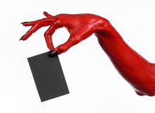 Halloween theme: Red devil hand with black nails holding a blank black card on a white background Royalty Free Stock Images