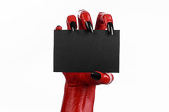 Halloween theme: Red devil hand with black nails holding a blank black card on a white background Stock Photo