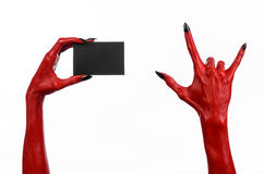 Halloween theme: Red devil hand with black nails holding a blank black card on a white background. Studio Royalty Free Stock Photography