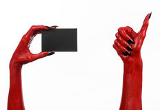 Halloween theme: Red devil hand with black nails holding a blank black card on a white background. Studio Royalty Free Stock Photos