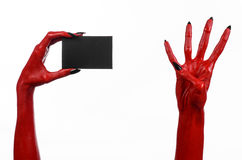 Halloween theme: Red devil hand with black nails holding a blank black card on a white background. Studio Stock Image