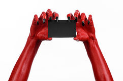 Halloween theme: Red devil hand with black nails holding a blank black card on a white background Stock Images