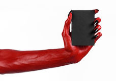 Halloween theme: Red devil hand with black nails holding a blank black card on a white background Stock Photos