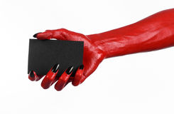 Halloween theme: Red devil hand with black nails holding a blank black card on a white background Royalty Free Stock Photography
