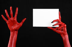 Halloween theme: Red devil hand with black nails holding a blank white card on a black background Stock Photos