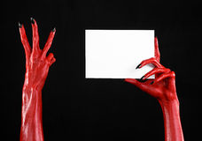 Halloween theme: Red devil hand with black nails holding a blank white card on a black background Royalty Free Stock Photography