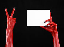 Halloween theme: Red devil hand with black nails holding a blank white card on a black background. Studio Royalty Free Stock Photos