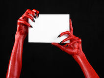 Halloween theme: Red devil hand with black nails holding a blank white card on a black background. Studio Stock Photography