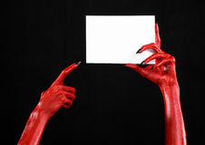 Halloween theme: Red devil hand with black nails holding a blank white card on a black background Royalty Free Stock Photos