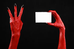 Halloween theme: Red devil hand with black nails holding a blank white card on a black background Stock Image