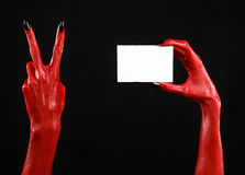 Halloween theme: Red devil hand with black nails holding a blank white card on a black background. Studio Stock Photo