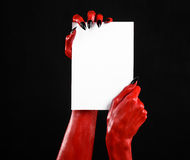 Halloween theme: Red devil hand with black nails holding a blank white card on a black background Stock Images
