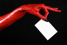 Halloween theme: Red devil hand with black nails holding a blank white card on a black background Royalty Free Stock Images
