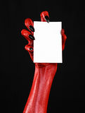 Halloween theme: Red devil hand with black nails holding a blank white card on a black background. Studio Stock Image
