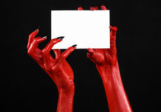 Halloween theme: Red devil hand with black nails holding a blank white card on a black background Stock Photography