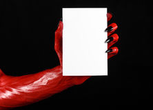 Halloween theme: Red devil hand with black nails holding a blank white card on a black background. Studio Royalty Free Stock Image