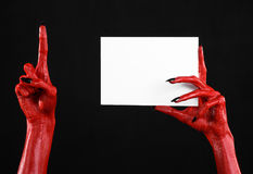 Halloween theme: Red devil hand with black nails holding a blank white card on a black background. Studio Royalty Free Stock Images