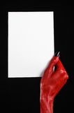 Halloween theme: Red devil hand with black nails holding a blank white card on a black background. Studio Stock Images