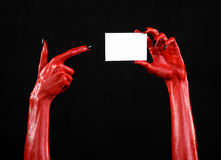 Halloween theme: Red devil hand with black nails holding a blank white card on a black background Stock Photo