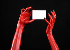 Halloween theme: Red devil hand with black nails holding a blank white card on a black background. Studio Stock Photos