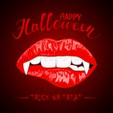 Halloween theme with red female lips and vampire fangs Royalty Free Stock Image