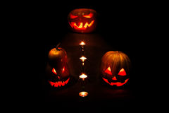 Halloween three pumpkins, one on the altar and two as servants a. T the altar with candles in the dark Royalty Free Stock Photography