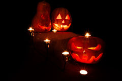 Halloween three pumpkins, one on the altar and two as servants a. T the altar with candles in the dark Royalty Free Stock Photos