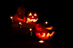 Halloween three pumpkins, one on the altar and two as servants a. T the altar with candles in the dark Royalty Free Stock Images