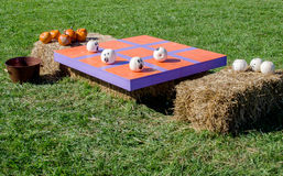 Halloween tic tac toe game. A unique outdoor game for a Halloween or fall party. Paint small pumpkins in white and orange, make a tic tac toe table from wood royalty free stock photo