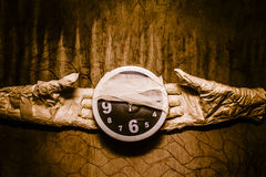 Halloween time. Mummy hands showing bandaged clock on grunge copy space wall. Halloween time, coming soon Royalty Free Stock Photos