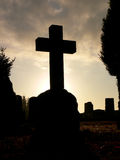 Halloween Tombstone. The sun setting behind a crossshaped tombstone on a graveyard at Halloween Royalty Free Stock Image