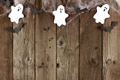 Halloween top border of spiderwebs, and ghost & bats on wood Royalty Free Stock Image