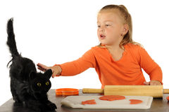Halloween Touch. An adorable preschooler playing with modeling dough cautiously reaching out to touch a scary black cat Stock Photos