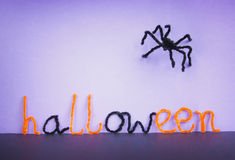 Halloween toy spider, pipe cleaners. Toy spider made of pipe cleaners and the word Halloween spelled with letters made of pipe cleaners. Orange, black and stock photos