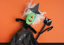 Halloween toy witch and black cat on orange. Halloween toys, witch made of a wooden spoon, tissue paper and pipe cleaners and a cat made of an old pencil and royalty free stock photo