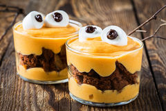 Halloween treats, little monster dessert. With chocolate cookies and orange mascarpone cream  topped with big marshmallow eyes Stock Image
