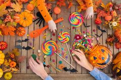 Halloween trick or treat candy and pumpkin. Family with child carving Halloween pumpkin and eating trick or treat candy on wooden table with autumn leaves stock photography