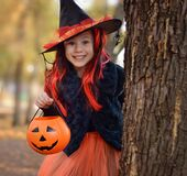 Halloween trick or treat.Happy girl wearing a witch`s hat, with a pumpkin handbag, peeps out from behind a tree.. Funny kid in