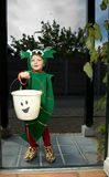 Halloween Trick or Treat Kid. Cute little boy (3) dressed as green baby dragon playing trick or treat at a door at Halloween Royalty Free Stock Image
