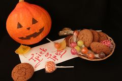 Halloween trick or treat load on a dark farm table, candy stock photo