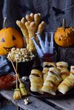 Halloween trick or treat party. Funny delicious food and pumpkin on wooden background - mini pizza, bread sticks, cheese, olives,. Ketchup, popcorn, juice. Copy royalty free stock photo