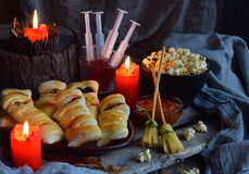 Halloween trick or treat party. Funny delicious food and pumpkin on wooden background - mini pizza, bread sticks, cheese, olives,. Ketchup, popcorn, juice. Copy royalty free stock images